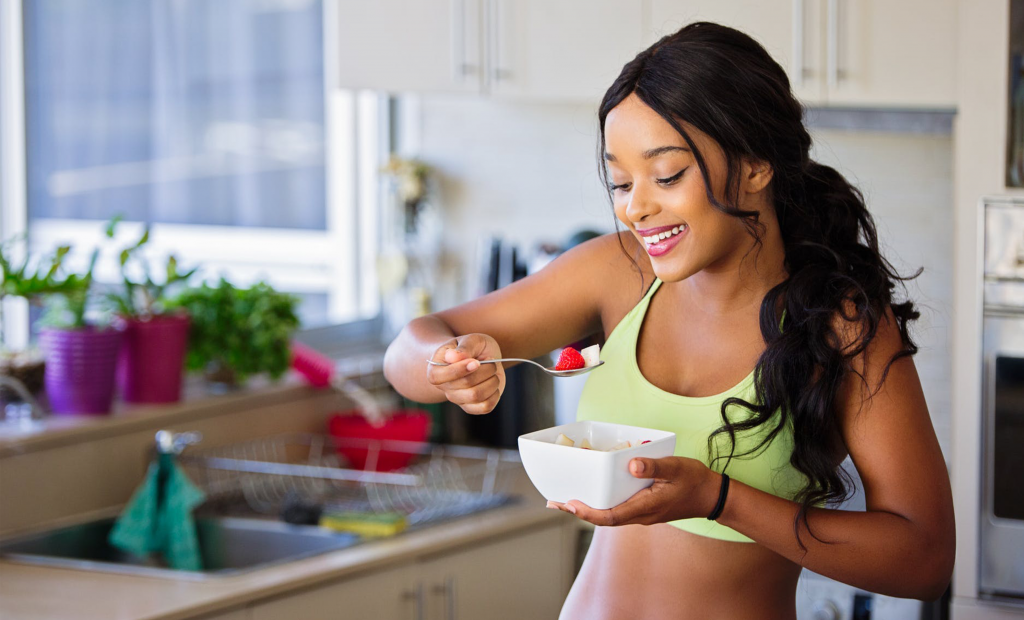 woman eating a bowl of fruits