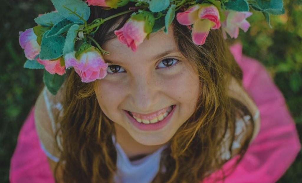 kid wearing a flower crown while smiling