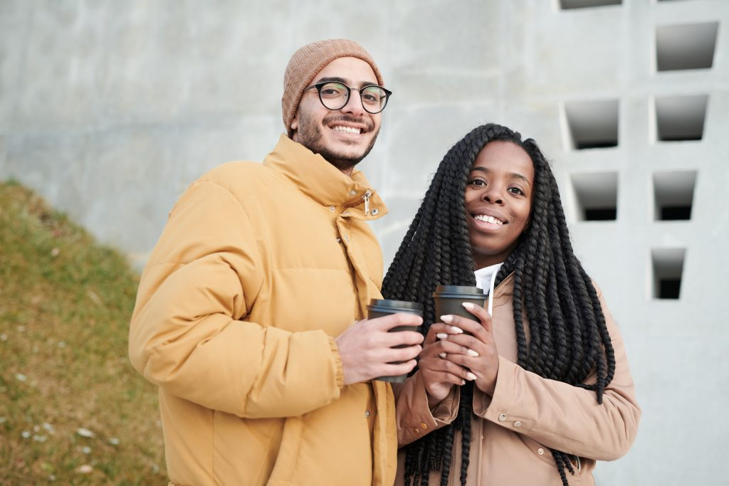 a man and a woman is holding a cup of coffee