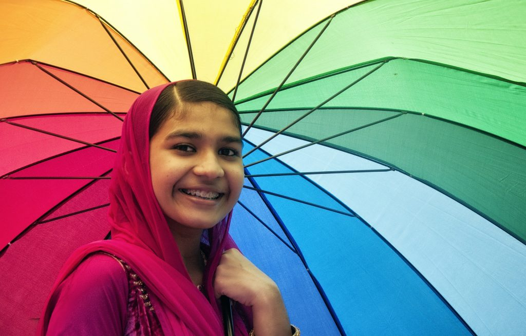 a girl with braces is holding a colorful umbrella