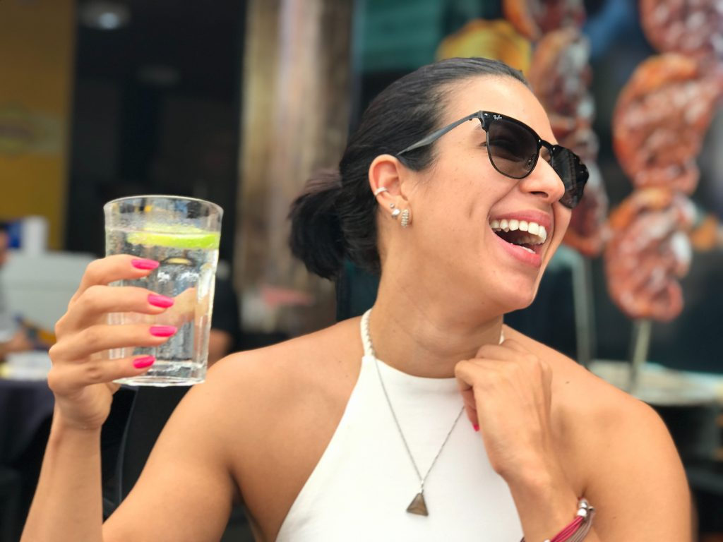 a happy woman with sunglasses is holding a glass of water
