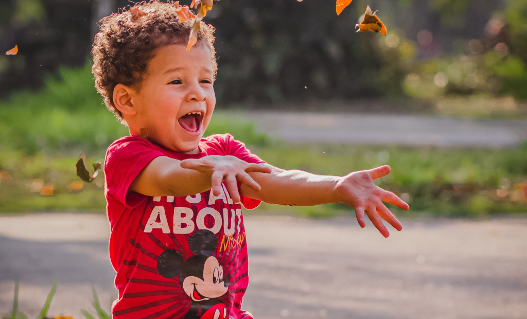 a kid wearing a red shirt is playing with leaves