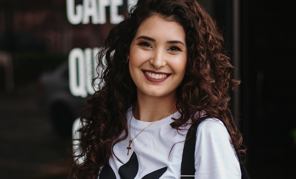 a curly-haired woman is smiling