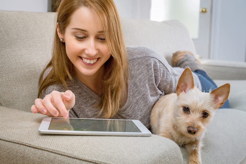a woman browsing through her tablet with her dog