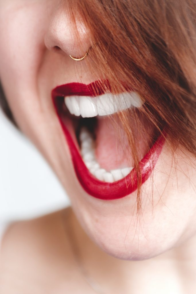 woman with nose piercing is wearing a red lipstick