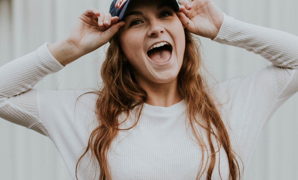 cheerful girl with a hat is wearing a white long sleeves