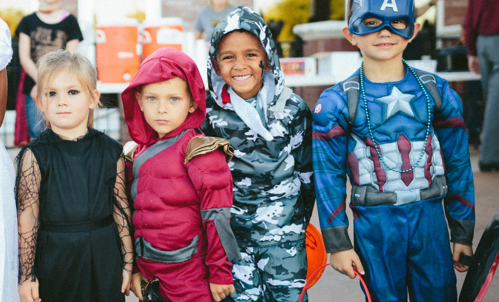 happy kids wearing super hero costumes