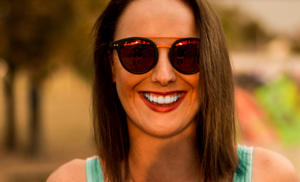woman with sunglasses is showing off her white teeth