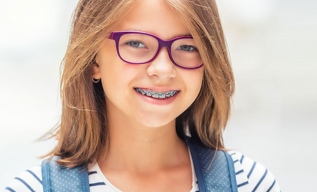 a pretty girl with violet eyeglasses is wearing a braces