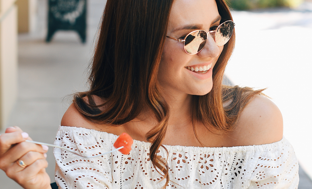 a happy woman with sunglasses is wearing a white lace off shoulder