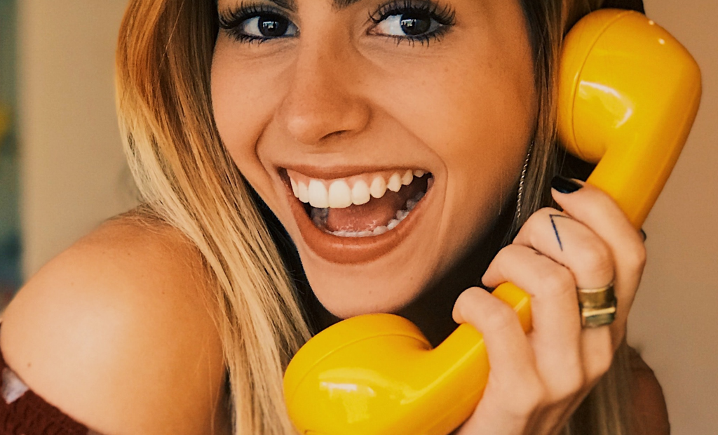 close up shot of a woman answering a yellow telephone