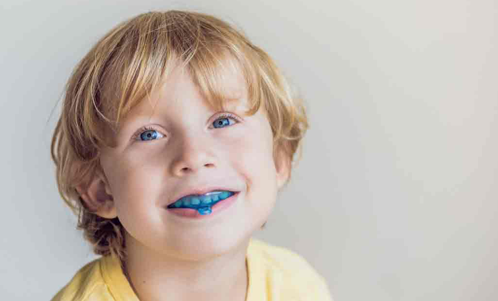 a kid with blue eyes wearing blue invisalign aligner