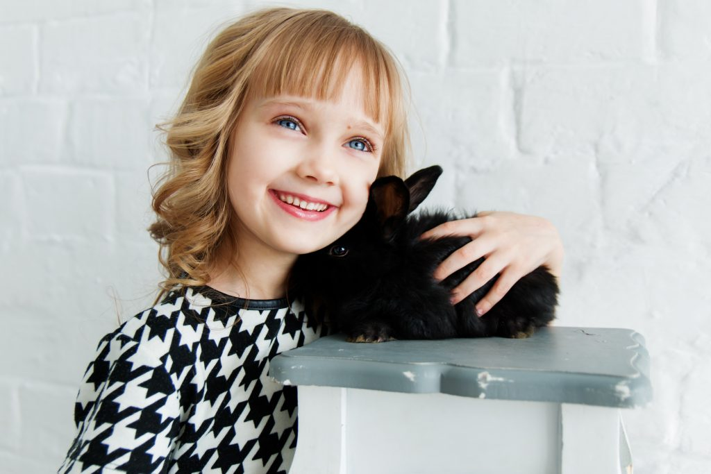 kid holding black rabbit