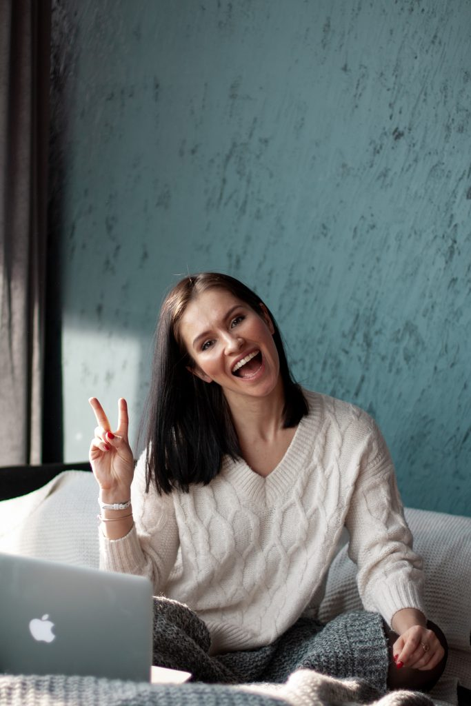 woman with white knit top showing peace sign