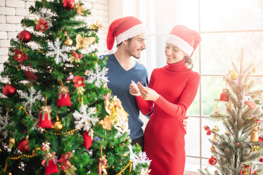 a couple standing beside the Christmas tree wearing Santa hat