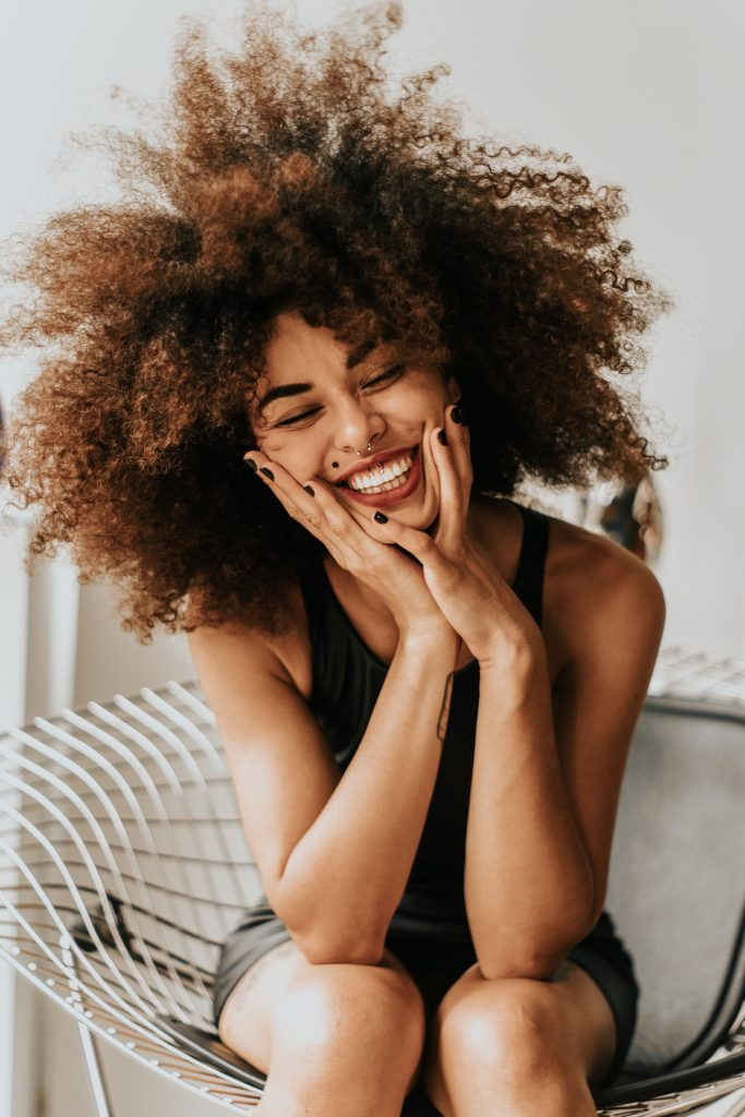 woman with a curly hair sitting and smiling
