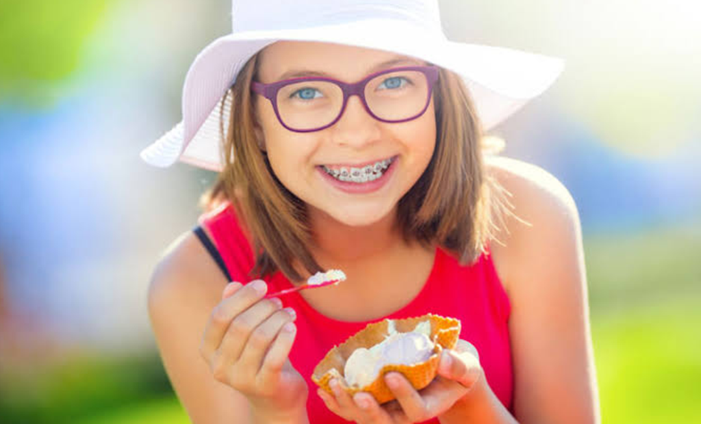 a girl with white summer hat is eating an ice cream