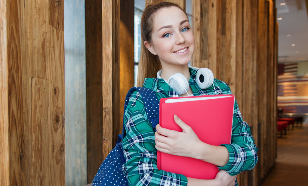 girl with blue eyes holding a red clear book
