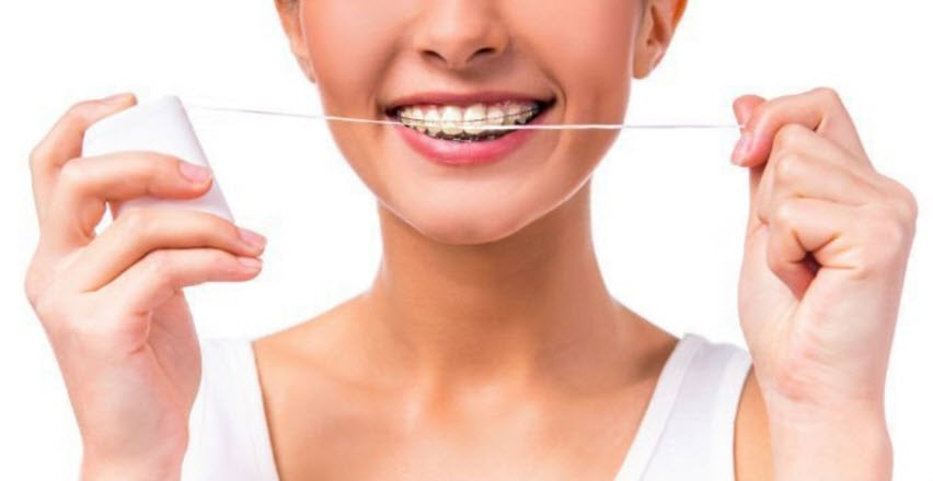 person with a retainer holding a dental floss