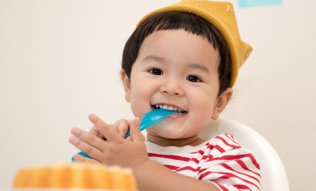 a toddler biting a rubber fork