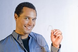 happy man holding clear aligners